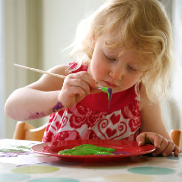 A girl painting a fundraising Christmas Card for School