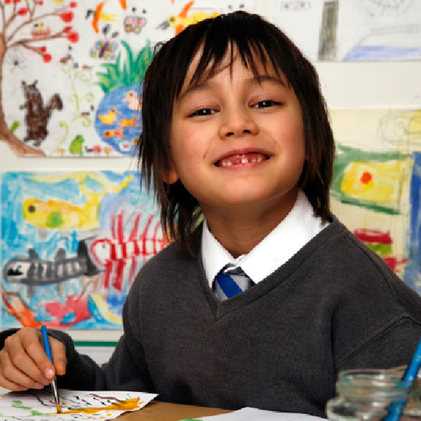 A boy painting a fundraising Christmas Card for School